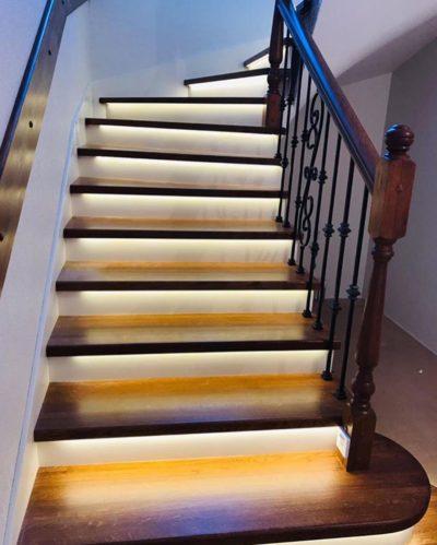 Лестница на бетоне обшитая дубом с коваными балясинами и подсветкой