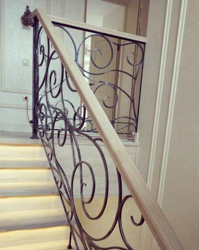 Лестница из ясеня с подсветкой и кованым ограждением
