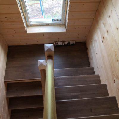 Лестница из бука в брусовом доме с широкой пригласительной ступенью