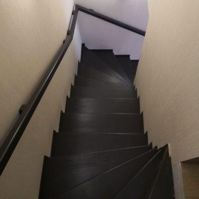 Черно-белая лестница в таунхаус с поручнем по стене