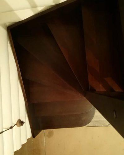 Темно-коричневая Г-образная лестница из ясеня в доме из бревна